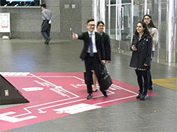 床サインを使って外国人を案内する様子